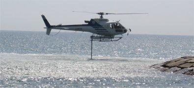 Elicottero in volo stazionario carica l' acqua dal mare